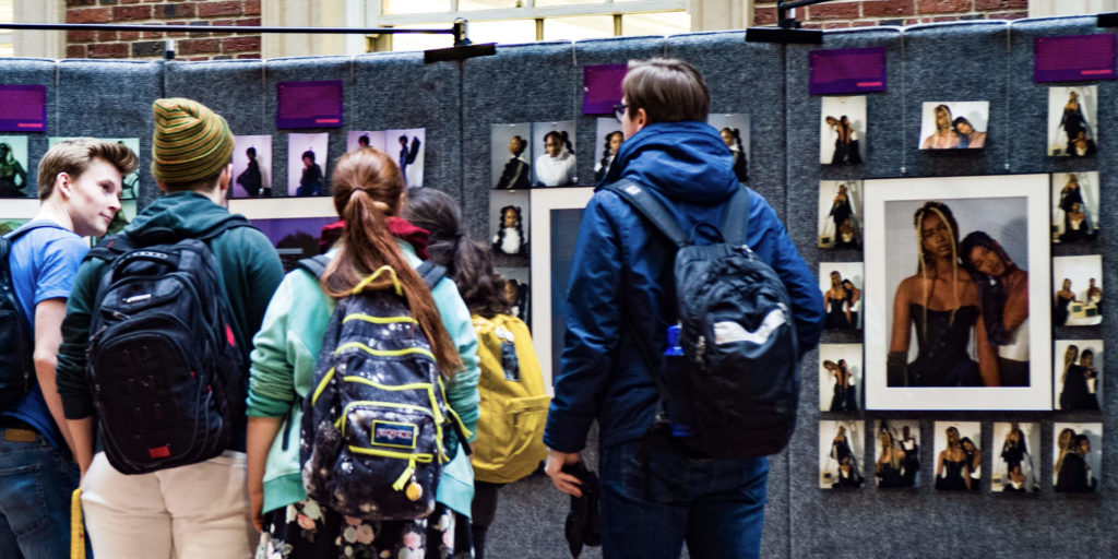 Five Students reviewing photo exhibit
